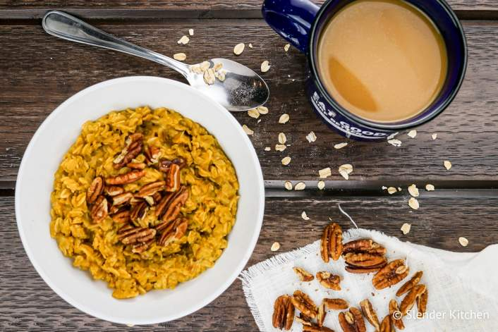 Pumpkin Pie Oatmeal with a spoon, loose oats, and pecans along with coffee.