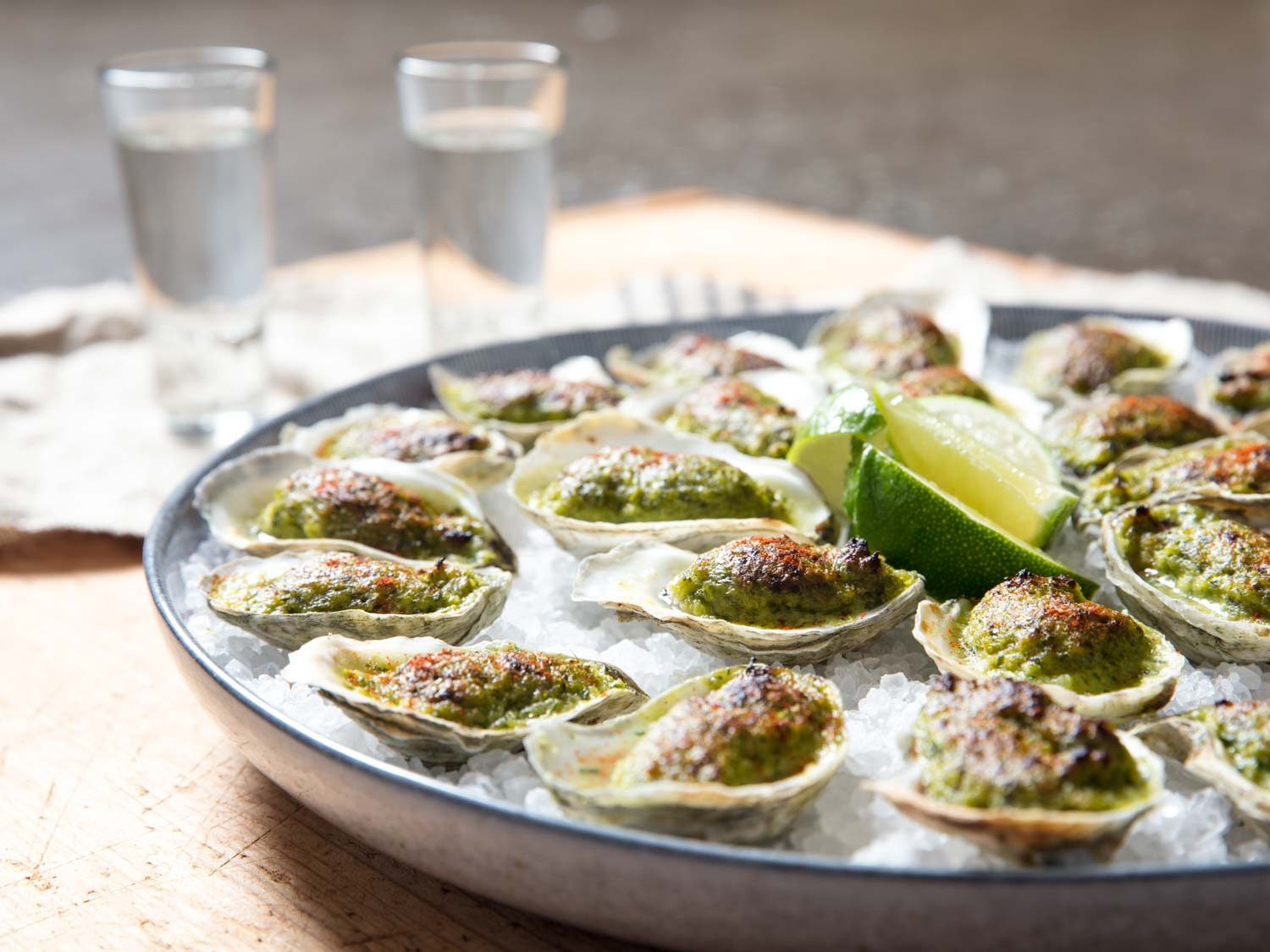 Side view of platter of oysters Oaxacafeller with glasses of mezcal.