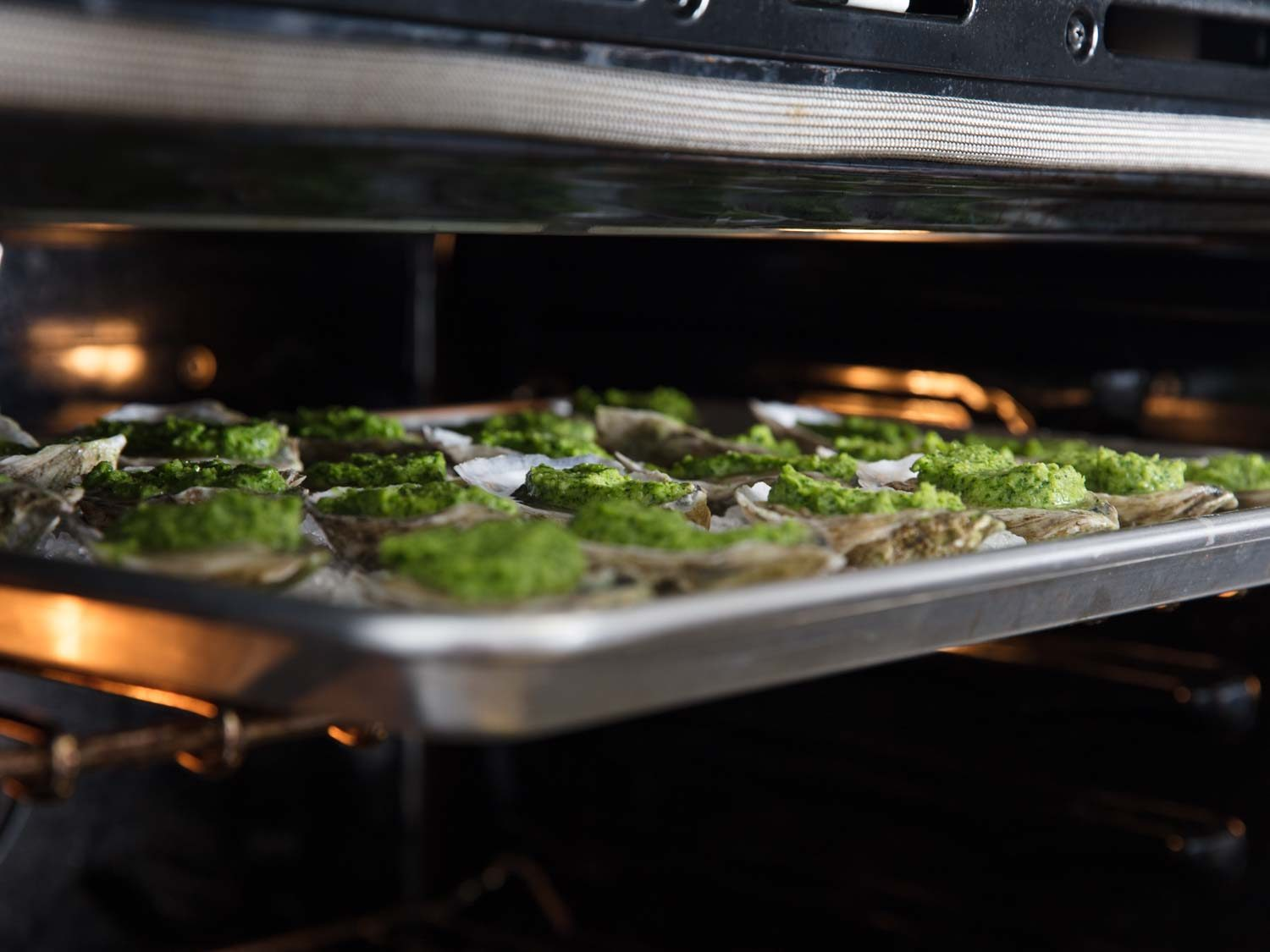 Oysters Rockefeller being placed under broiler.