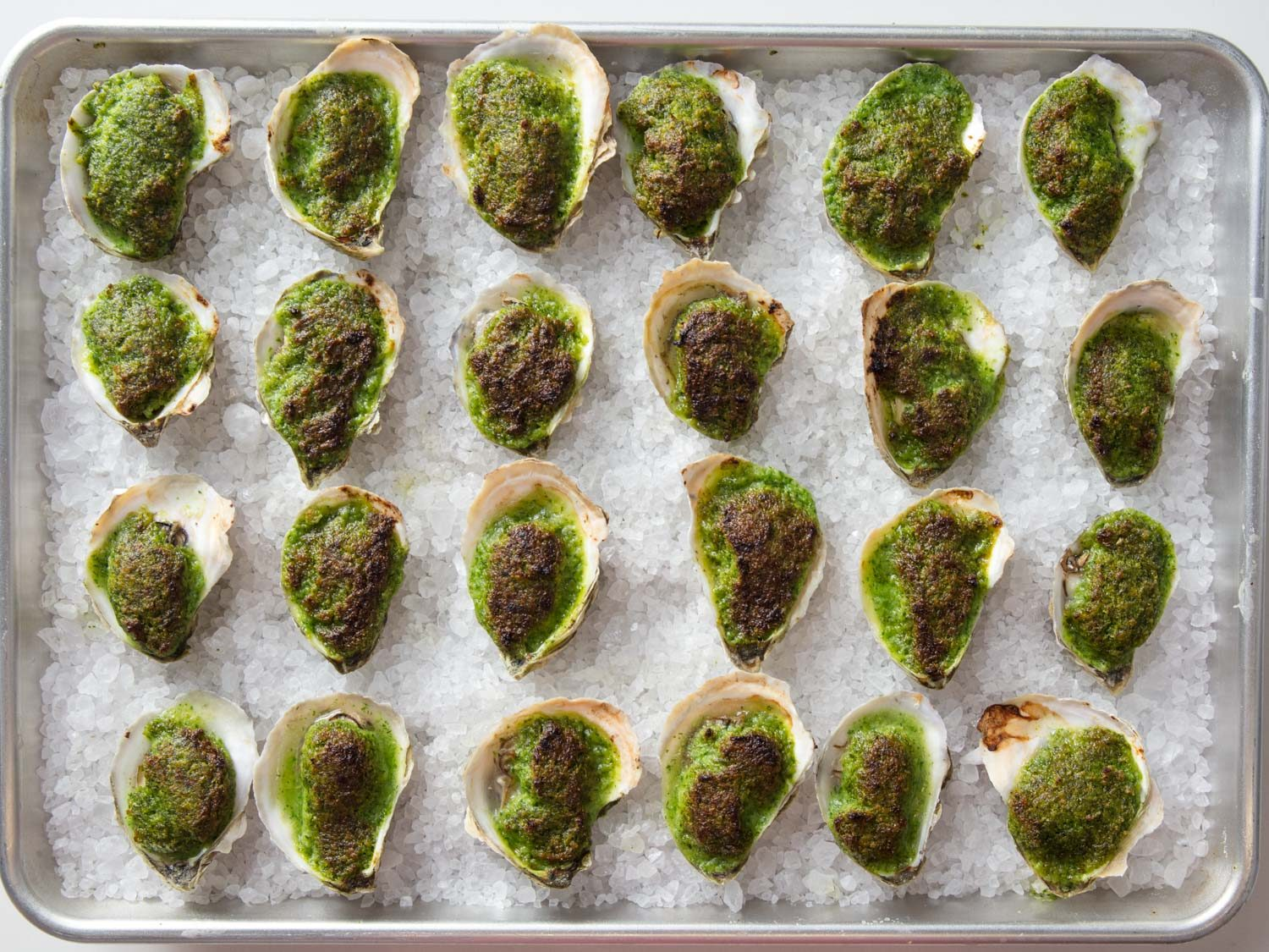 Overhead shot of baking sheet full of oysters Rockefeller.
