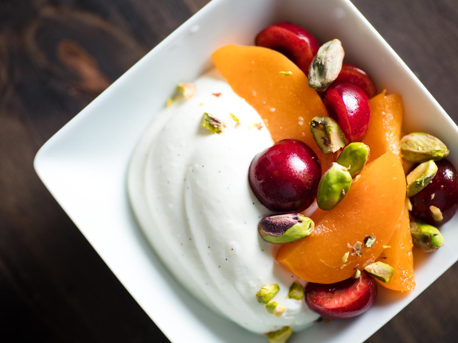 Whipped Greek yogurt with pistachios, cherries, and apricots in a white dish